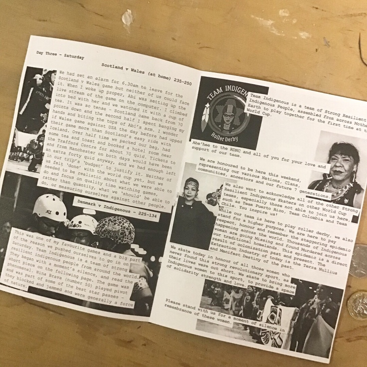 A black and white, A5 cut and paste zine about roller derby lies open on a table.
