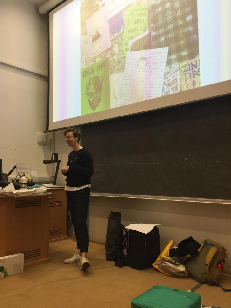 A white non-binary person with short brown hair is standing, grasping their hands together, at the front of a lecture theatre. On the board behind them, an image of zines lying on top of each other is projected.