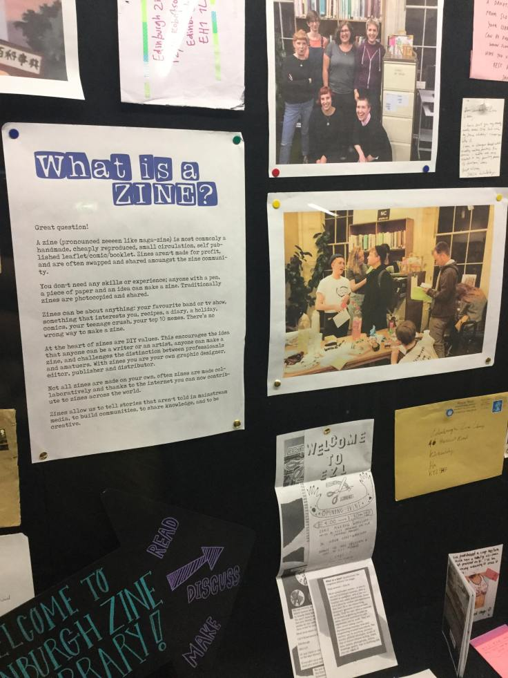A display board, with photos of zine library events tacked to it, envelopes, and a poster that reads 'Whats A Zine?' with the rest of the text too small to be legible.