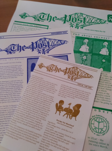 a flat lay of three single sheet risoprinted zines, in green blue and matte gold, each with the heading 'the post'